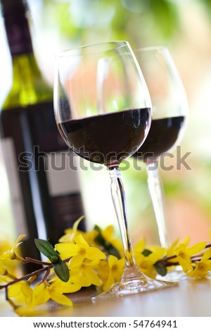 to wine glasses filled with red wine and wine bottle in background