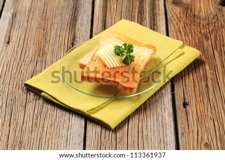 Toast and butter on a glass plate