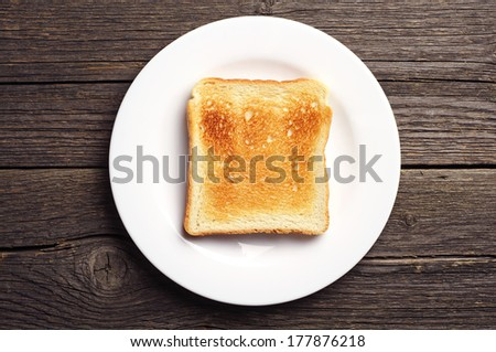 Toast bread in a white plate on vintage wooden background. Top view