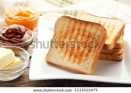 Toast bread in plate with bowls of butter and jam on wooden table ストックフォト ©