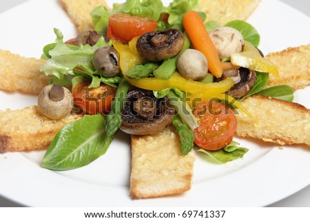 Toast fingers topped with parmesan and served with a salad of grilled cherry tomatoes, various mushrooms, asparagus, baby carrots, capsicum and lettuce