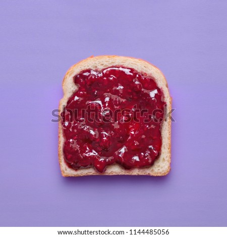 Toast slice with fruit jam on a purple background viewed from above. Slice of bread with raspberry marmalade isolated on a colorful background. Top view #1144485056