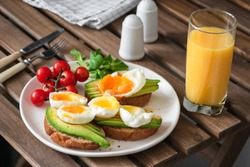 Toast with avocado, egg and glass of orange juice on a wooden table. Healthy eating, healthy lifestyle concept