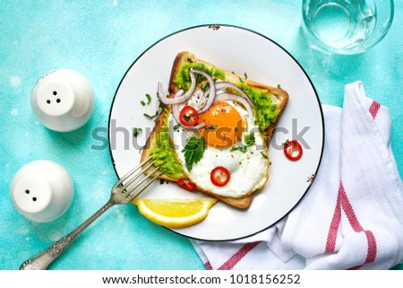 Toast with avocado (guacamole), fried egg and spices for a brakfast on a vintage plate over turquoise slate background.Top view.