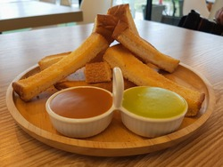 toast with butter served with two sauces. grilled bread with two-color custard pandan. on a wooden plate, colorful delicious.