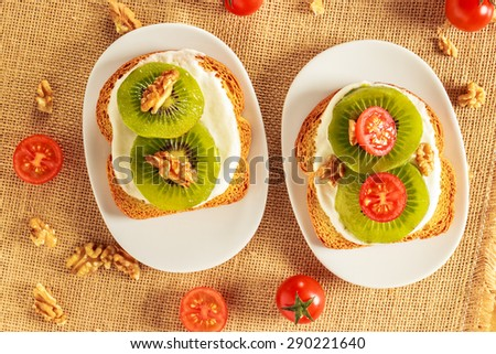 Toast with kiwi, cheese, walnuts and cherry tomato  on a piece of sackcloth with walnuts and cherry tomatoes around. View from above