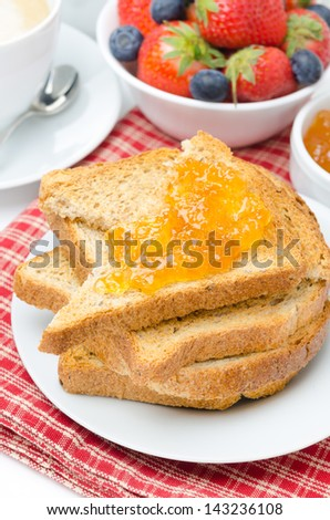 toast with orange jam and fresh berries for breakfast close-up