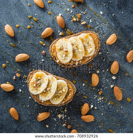 Toast with peanut butter, banana and almond nuts on dark table. Diet natural breakfast. Flat lay, top view