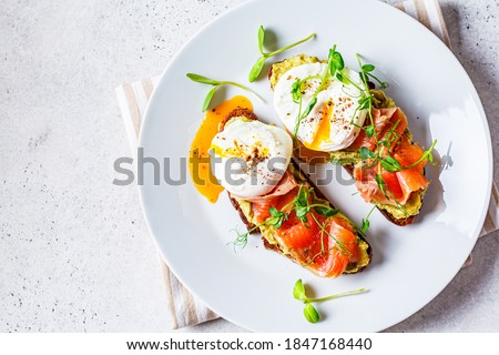 Toast with salmon, poached egg and avocado on a white plate. Poached egg with salmon and guacamole on rye bread.