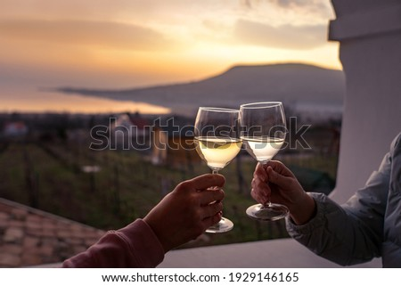 toast with wine glasses at lake Balaton with the Badacsony hill in the background . Stock photo ©