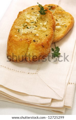 Toasted baguette slices with butter, garlic and herbs.