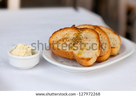 Toasted bread with garlic and spices on a white plate and butter