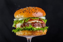 Toasted brown hamburger with mushrooms champignons, mozzarella cheese, tomato sauce, a piece of fried bacon, juicy steak from pork or beef, greens and tomato wooden chopping board, Isolated