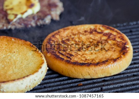 Toasted burger for a hamburger. The biscuit is baked on the grill. Making a hamburger.