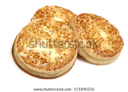 Toasted crumpets with butter on white background.