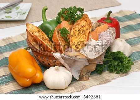 Toasted garlic bread in a basket with capsicums and parsley laid on a checkered mat.
