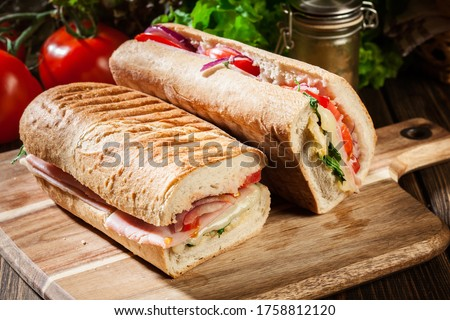 Toasted panini with ham, cheese and arugula sandwich on cutting board Stok fotoğraf ©