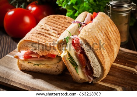 Toasted panini with ham, cheese and arugula sandwich on cutting board