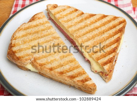 Toasted sandwich with beef pastrami and melting cheese