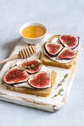 Toasted whole wheat bread with figs, ricotta (cream cheese), thyme, honey served on white wooden rustic cutting board. Healthy food concept. Light blue stone background. Top view.
