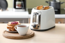 Toaster with bread slices and cup of coffee on table