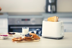 Toaster with dishes and sandwiches on a light kitchen table