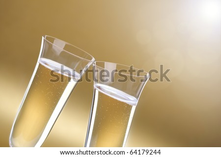 Toasting a celebration with champagne glasses on gold background for copy
