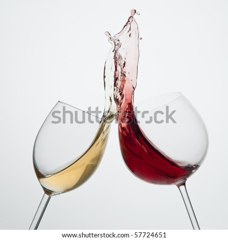 Toasting gesture red and white wine with big splash big splash