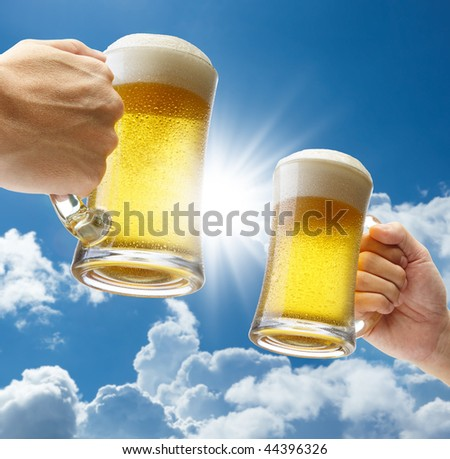 toasting with beers against clear blue sky