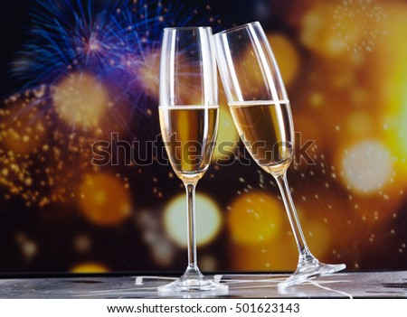 toasting with champagne glasses against holiday lights and new year fireworks #501623143