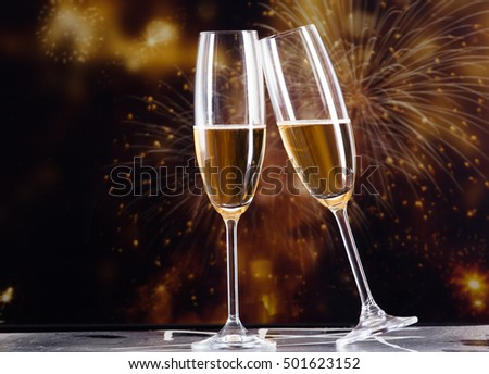 toasting with champagne glasses against holiday lights and new year fireworks #501623152