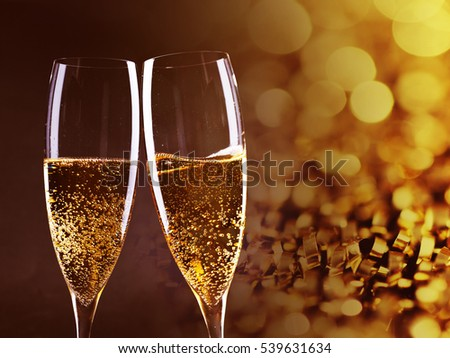 toasting with champagne glasses against holiday lights and new year fireworks #539631634