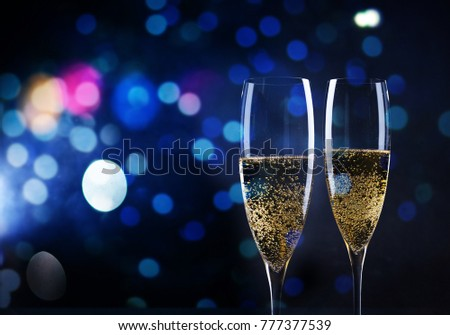 toasting with champagne glasses against holiday lights and new year fireworks #777377539