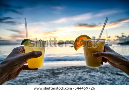 Toasting with tropical drinks at sunset with island beach background; focus on drinks