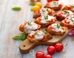 Toasts, bruschetta with tomatoes, mozzarella cheese and fresh basil on a chopping board on a wooden table. Delicious appetizer or breakfast