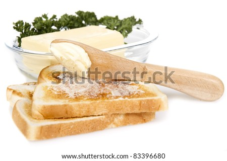 Toasts with butter and knife over white background