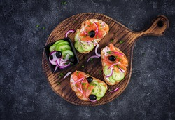 Toasts with cream cheese, smoked salmon, cucumber and red onion on dark  table. Open sandwiches. Healthy care, super food concept. Top view, overhead