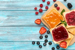 Toasts with jam and cutting board on blue wooden table