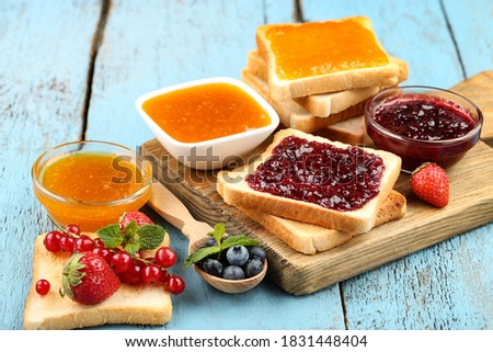 Toasts with jam with fresh berries on blue wooden table ストックフォト ©