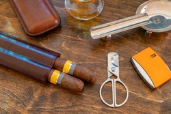 Tobacco and alcohol. Cigar and brandy on a wooden table, top view. Cuban quality brand cigars and rum, smoking and drinking luxury lifestyle