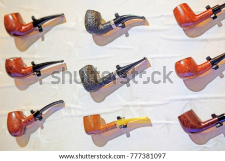 tobacco pipe hangs on the wall #777381097
