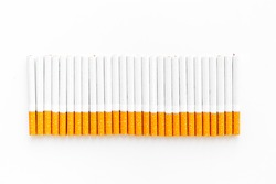 Tobacco. Row of cigarettes on white background top view