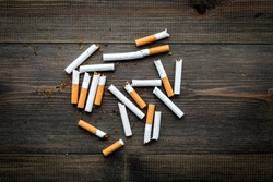 Tobacco. Scattered cigarettes on dark wooden background top view copy space