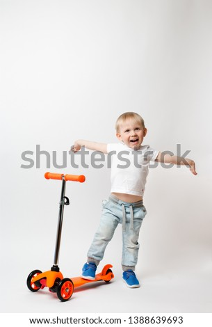 Toddler, a very joyful child, raised his hands in awe of the scooter's gift. Concept for advertising and articles about toys and bicycles on a white background #1388639693