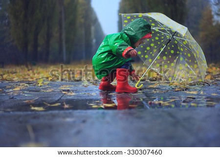 Toddler and umbrella in autumn rainy park - stock photo