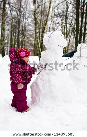 toddler baby child with snowman in winter park