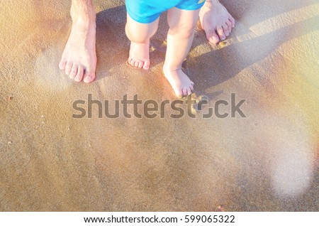 Toddler baby doing his first steps on the beach. Bare feet father and son staying on the sand near the bank in sunny day. Summertime holidays concept. Top view. Copy space.