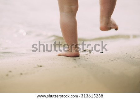 Toddler baby doing his first steps on the sand near the bank
