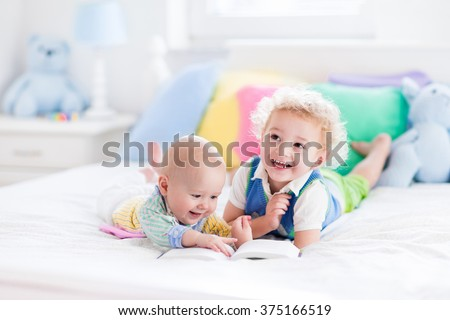 Toddler boy and baby reading a book in parents bed. Children read books in white bedroom. Kids playing together. Siblings bonding. Nursery toys and textile in pastel colors. Brothers kiss and hug.