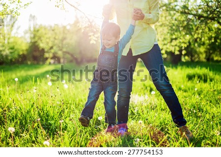 Toddler boy and his mom having fun in summer park, Image with backlight, some stay light in foreground - stock photo